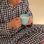 寝付けずホットミルクを飲む男性
